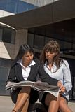 Coeds looking at a newspaper. Two students sitted women and reading the newspaper Stock Image