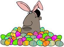 Coelhinho da Páscoa étnico em uma pilha de ovos decorados Imagem de Stock
