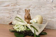 Coelhinho da Páscoa com o ovo da páscoa no ninho contra o fundo de madeira como um cumprimento da Páscoa Fotos de Stock Royalty Free
