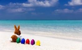 Coelhinho da Páscoa com ovos da páscoa coloridos em uma praia Foto de Stock Royalty Free
