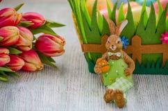Coelhinho da Páscoa com tulipas e ovos no vntage de madeira fotos de stock royalty free