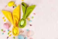 Coelhinho da Páscoa do guardanapo, ovos da decoração e doces da Páscoa no fundo cor-de-rosa fotos de stock