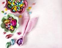 Coelhinho da Páscoa do guardanapo, ovos da decoração e doces da Páscoa no fundo cor-de-rosa fotografia de stock