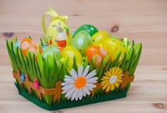 Coelhinho da Páscoa feliz com ovos em uma cesta e imagem de stock royalty free