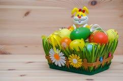 Coelhinho da Páscoa feliz com ovos em uma cesta no fotografia de stock royalty free