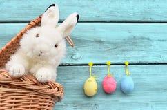 Coelhinho da Páscoa feliz na cesta e ovos no fundo azul Imagem de Stock