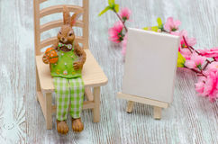 Coelhinho da Páscoa que senta-se no tamborete com um ovo, uma armação de pintura e umas flores sobre o fundo de madeira imagens de stock royalty free