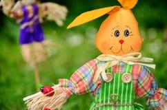 Coelhinho da Páscoa vestido para a decoração em um jardim verde da mola Imagem de Stock