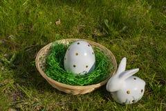 Coelhinho da P?scoa e um ovo da p?scoa feito da cer?mica branca com ?s bolinhas dourados com uma cesta em um prado imagem de stock