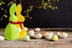 Coelhinhos da Páscoa feitos a mão e ovos na tabela de madeira foto de stock