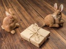 Coelhinhos da Páscoa no fundo da tabela de madeira das placas idosas com a caixa de presente amarrada com corda Fotos de Stock