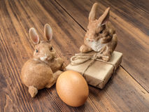 Coelhinhos da Páscoa no fundo da tabela de madeira das placas idosas com a caixa de presente amarrada com corda e a galinha marro Foto de Stock Royalty Free