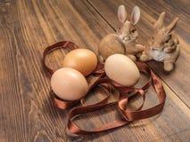 Coelhinhos da Páscoa no fundo da tabela de madeira das placas idosas com fita e os ovos marrons da galinha Foto de Stock Royalty Free