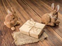 Coelhinhos da Páscoa no fundo da tabela de madeira das placas idosas com serapilheira, caixa de presente amarrada com corda e mar Fotos de Stock