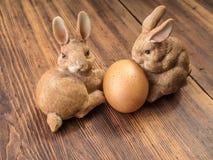 Coelhinhos da Páscoa no fundo da tabela de madeira das placas idosas com serapilheira e os ovos marrons da galinha Fotos de Stock