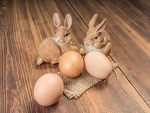 Coelhinhos da Páscoa no fundo da tabela de madeira das placas idosas com serapilheira e os ovos marrons da galinha Imagens de Stock