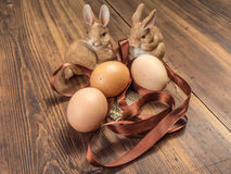 Coelhinhos da Páscoa no fundo da tabela de madeira das placas idosas com serapilheira, fita e os ovos marrons da galinha Imagem de Stock