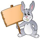 Coelho bonito que prende a placa de madeira ilustração do vetor
