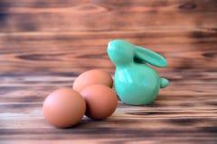 Coelho cerâmico da Páscoa com os ovos no fundo de madeira fotos de stock royalty free