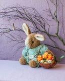 Coelho da peluche que senta-se com a cesta de rosas do en dos ovos Imagem de Stock Royalty Free