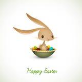 Coelho de Easter que senta-se na bacia completamente de ovos coloridos