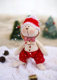 Coelho do brinquedo do Natal em árvores do fundo Fotografia de Stock Royalty Free