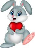 Coelho dos desenhos animados que guarda o coração vermelho Fotografia de Stock