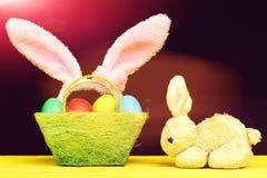 Coelho e cesta de Toy Easter completamente de ovos da páscoa coloridos Fotos de Stock