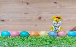 Coelho feliz com ovos da páscoa e grama no imagens de stock