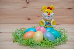Coelho feliz com ovos da páscoa em um ninho no imagem de stock