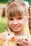 Coelho feliz da alimentação da menina com cenoura. Fotos de Stock Royalty Free
