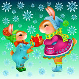 Coelhos bonitos dos desenhos animados com uma caixa de presente no fundo com flocos de neve Fotos de Stock Royalty Free
