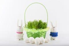 Coelhos de Toy Easter com cesta e os ovos verdes Foto de Stock Royalty Free