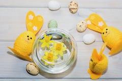 Coelhos decorativos da Páscoa com narcisos amarelos Imagens de Stock Royalty Free