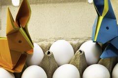 Coelhos do origâmi do papel colorido Lebres da Páscoa e ovos brancos da galinha em uma caixa imagens de stock royalty free