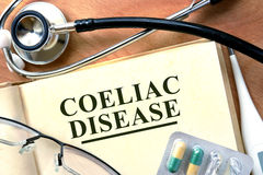 Coeliac disease. Word Coeliac disease  on a book and pills on the wooden table Stock Images