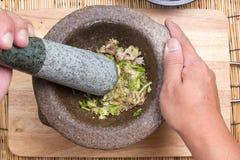 Coentro, pimenta e alho da libra do cozinheiro chefe com o pilão no almofariz Imagem de Stock