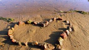 Coeur, établi des pierres, sur la banque arénacée de la rivière image stock