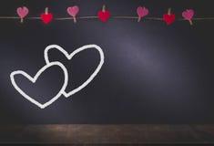 Coeur accrochant et coeur Drawed sur le fond avec l'espace de copie dedans Photographie stock libre de droits