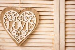 Coeur accrochant sur le fond en bois de texture Photographie stock libre de droits