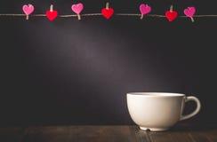 Coeur accrochant sur le fond et la tasse avec l'espace de copie dans Valentine Images stock