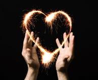 Coeur ardent de la paume d'une personne. Photo stock