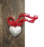 Coeur argenté, ruban de dentelle sur le vieux bois, d'isolement Photographie stock libre de droits