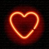 Coeur au néon sur le mur de briques Photos stock