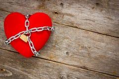 Coeur avec des chaînes sur le fond en bois Images stock
