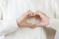 Coeur avec des mains la fille tient des mains sous forme de coeur Photo stock