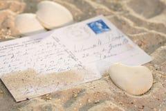 Coeur avec la carte postale dans le sable Photo stock