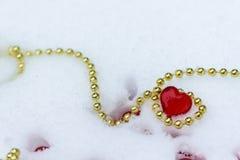 Coeur avec la chaîne d'or sur la neige la Saint-Valentin Fond d'image image stock