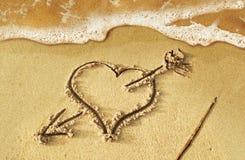 Coeur avec la flèche, comme signe d'amour, dessiné sur le rivage de plage, avec s Image stock