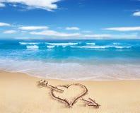 Coeur avec la flèche, comme signe d'amour, dessiné sur le rivage de plage, avec t Photos libres de droits
